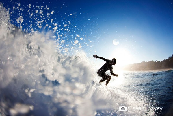 A surfer surfing away from the camera and towards the rising sun at Rocky Point.