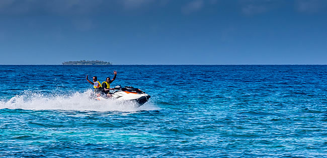 Waving natives in speed boat