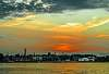 Sun disappears into the chimneys of Riga's left coast
