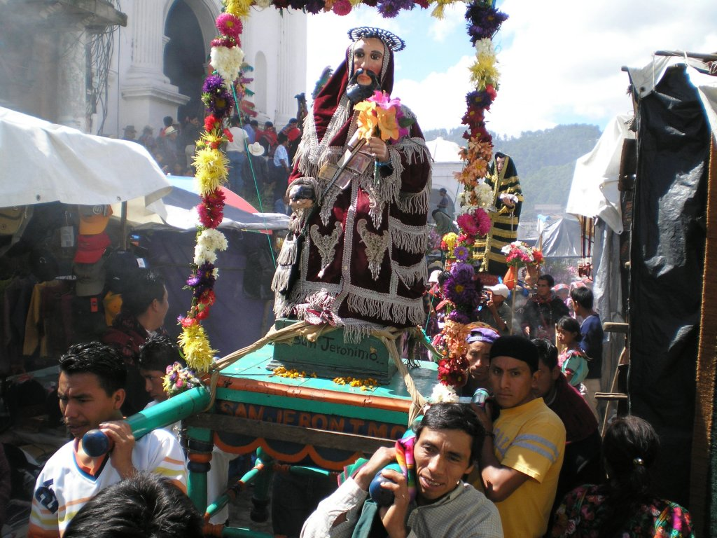 Chichicastenango market day procession. On Sundays there is a famous flower market on the steps of the church of Santo Tomas. Every hour or so there is a procession of saints through the street market below the church.