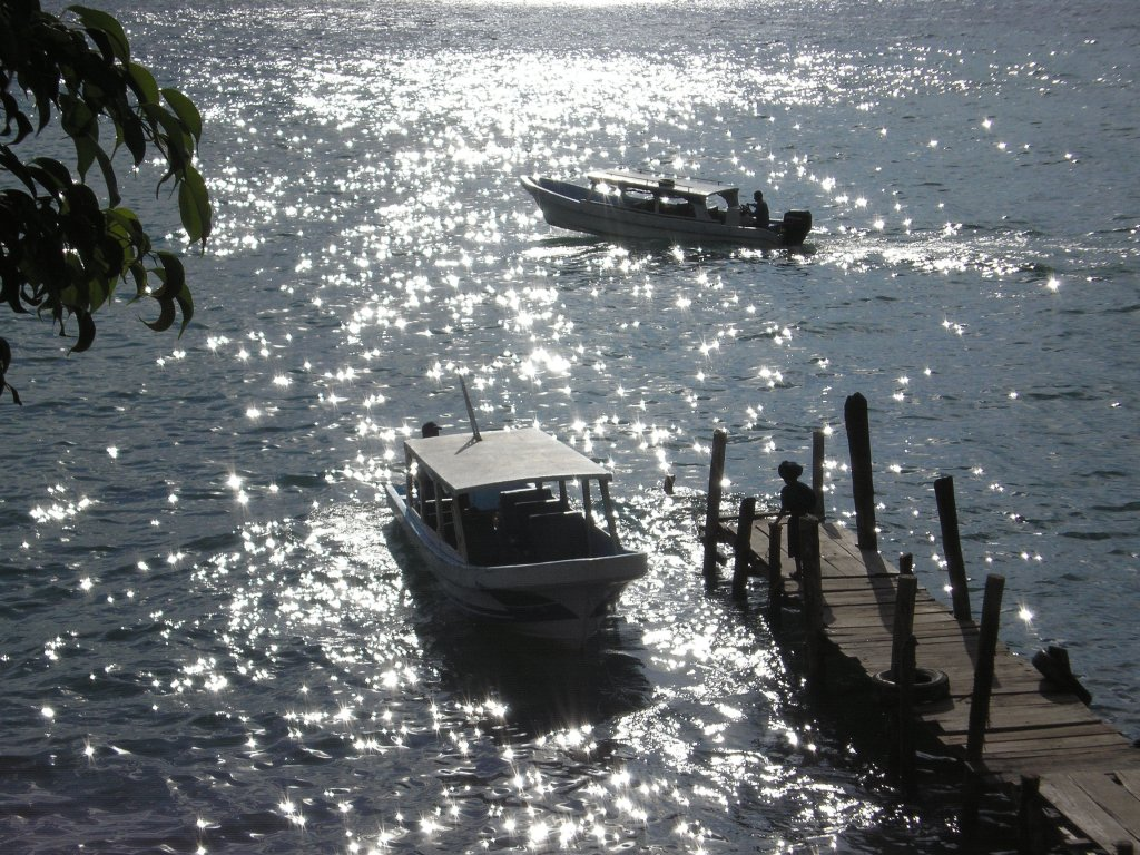 This is on the shores of Panajachel on Lake Atitlan. These boats are water taxis that run continuously to the outlying villages on the lake. Once they move away from the rickety docks, the operators hit the gas, the boat leaps forward and passengers hold on to their hats!