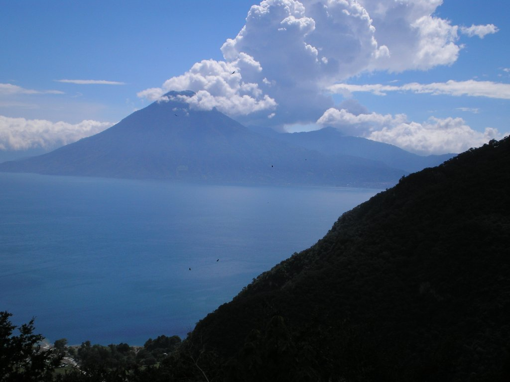 Lake Atitlan Volcano. There are seven volcanoes which ring the lake. During our time in the country, it seemed like there was an active volcano around every corner. In terms of composition, even the smoke from the volcano co-operates to create two diagonal lines - bottom left to top right - that is intersected by the distant shoreline which is horizontal. By the village on the lower left, you can see how high up we are on the mountain road. Roads are like this in Guatemala - if your car hops the curb, you can fall hundreds of feet before landing.